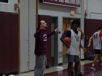 Naugatuck coach Mike Wilson gives out instructions as senior captain Keywan Garris looks on during last Friday's practice. In the background is sophomore Avery Hinnant. (Kevin Roberts/RA)