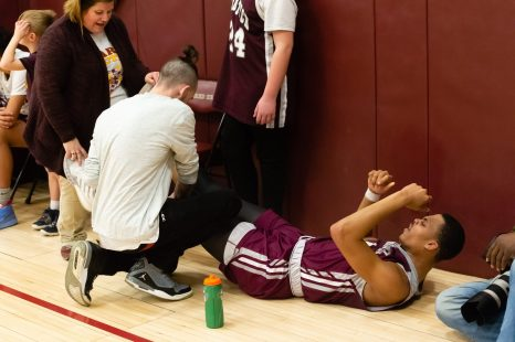 After cramping up, Naugatuck's Avery Hinnant (4) gets stretched out on the sidelines during their key NVL match-up against Sacred Heart Friday at Alumni Hall at Sacred Heart High School. Jim Shannon Republican-American
