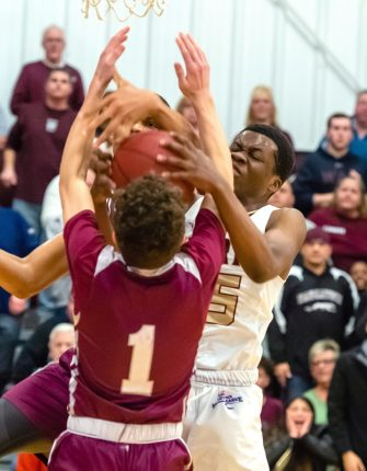 Sacred Heart's Osa Igbinewuare (25) pulls down a rebound in front of Naugatuck's Jay Barth (1) during their key NVL match-up Friday at Alumni Hall at Sacred Heart High School. Jim Shannon Republican-American