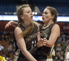 Thomaston's Gabby Hurlbert (11) is congratulated by teammate Nicole Schaefer (3) after getting fouled during their Class S state championship game with Canton Saturday at the Mohegan Sun Arena. Jim Shannon Republican-American
