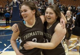 Thomaston's Nicole Schaefer (3) and seniors Sara LeVasseur (20) and Kathryn Miner (2), background, celebrate their 52-50 win over Canton to capture the Class S state championship Saturday at the Mohegan Sun Arena. Jim Shannon Republican-American
