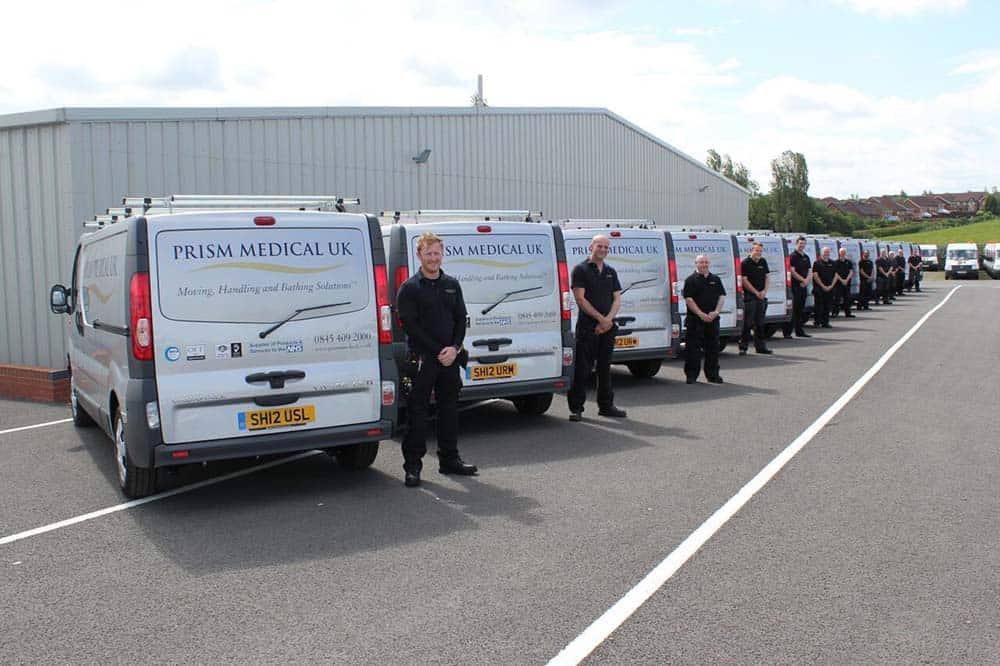 Prism Medical UK team standing outside vans