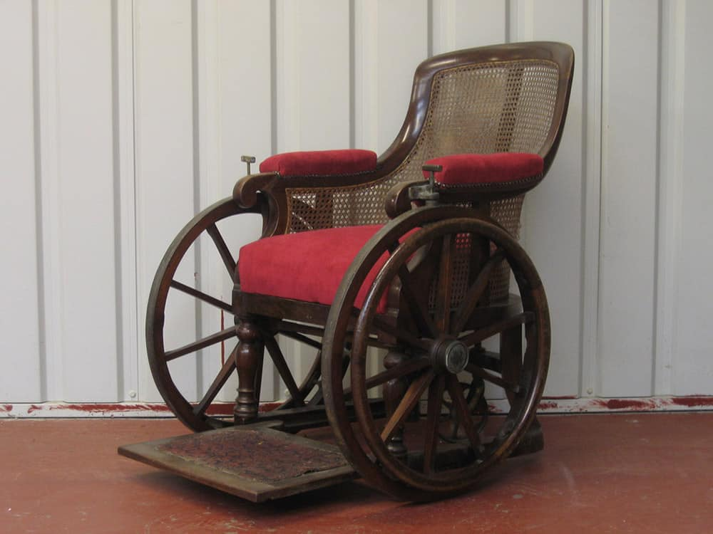 Antique wheelchair made from wood with red velvet