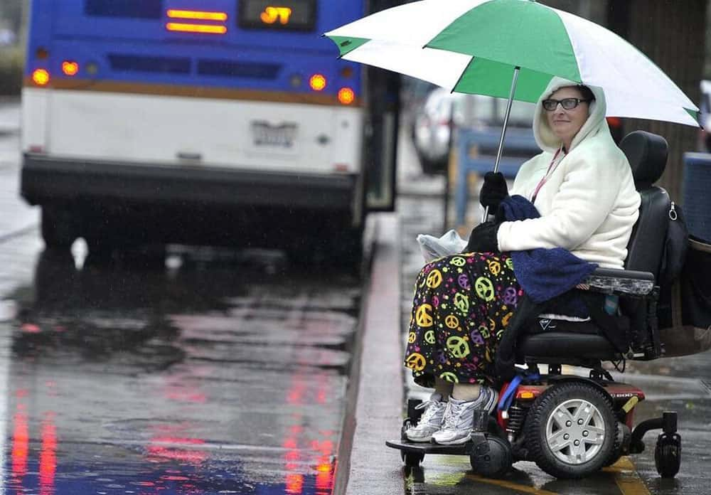 Mobility powerchair in the rain with user holding umbrella