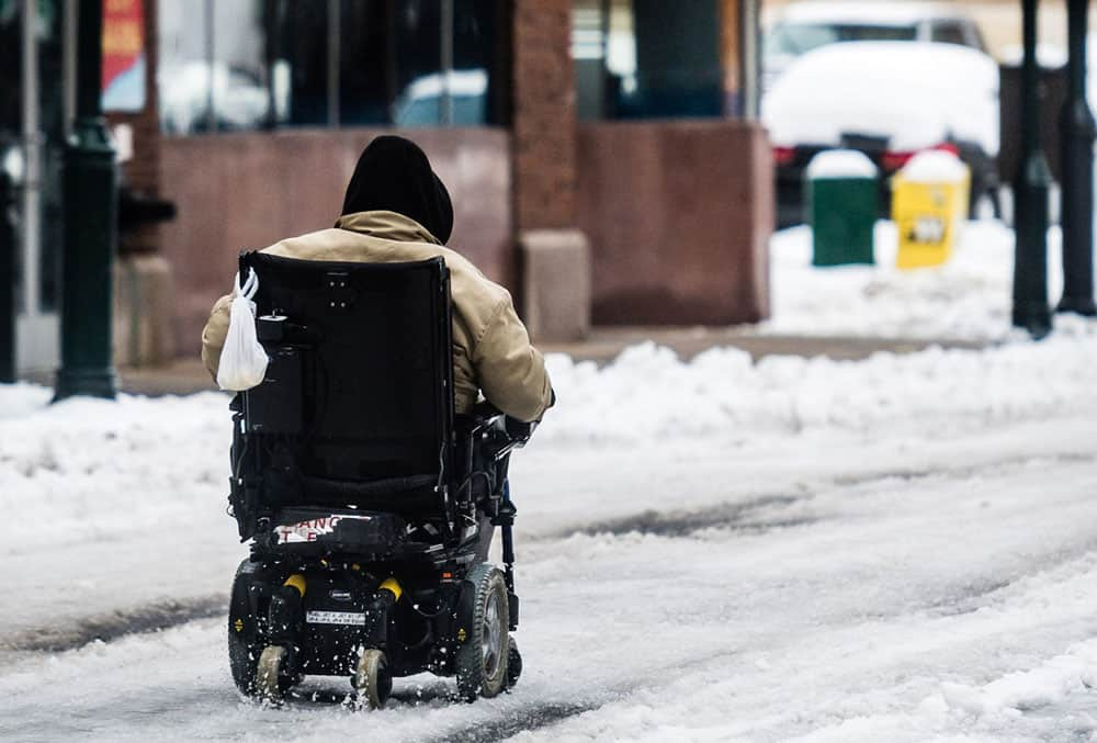 A mobility powerchair user riding in the snow