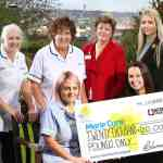 Acorn Stairlifts celebrate after raising £20,000 for Marie Curie outside