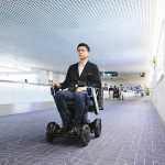 WHILL Haneda Trial man riding powerchair