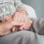 elderly person holding hands at home