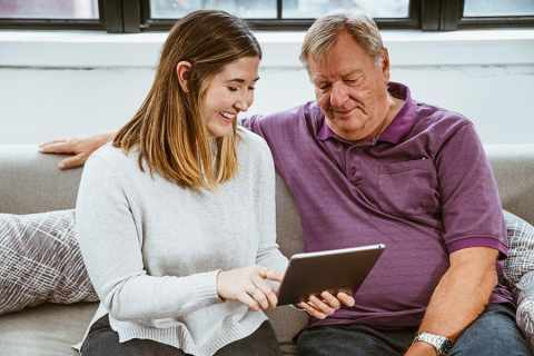 young woman and older man using technology
