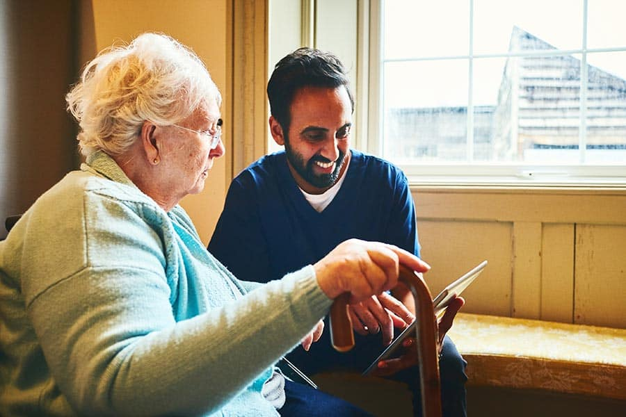 Male nurse showing a digital tablet to an elderly woman in a care home.
