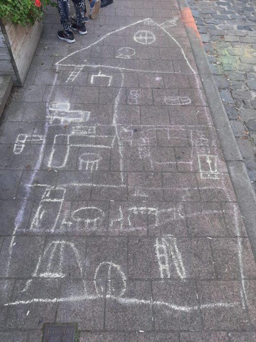 Krijttekening van en huis op het voetpad