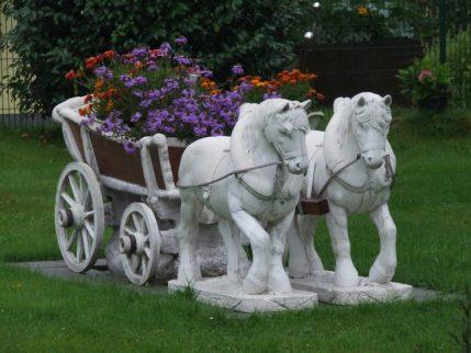 kitscherig beeld in een voortuin: twee paardjes met een kar