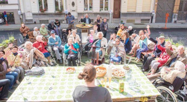 Groep ouderlingen rond een grote tafel op straat