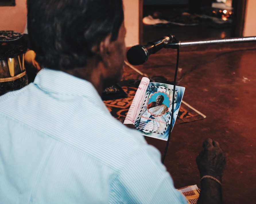 the funeral singer is reciting thevarams and letters from the family to our grandmother. The whole neighbourhood can hear his voice through big speakers. A copy of that booklet is given to everyone attending.