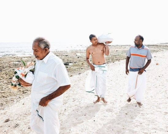 my uncles walking along the keerimalai beach before throwing the ashes into the indian ocean. The ashes are in the brown pot with the flower garland.