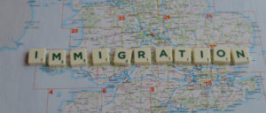 """""""immigration"""" spelled in Scrabble letters over a map of Britain"""
