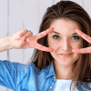 woman holding peace symbols to face
