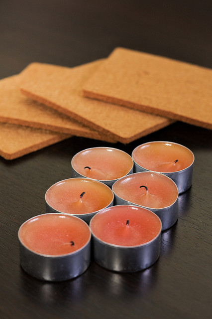 Six red aromatherapy candles wrapped in aluminum foil and having the tip of their wicks burnt already. They are sitting on a dark brown table which reflects their image. Behind them there are four coasters.