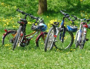 three bikes with helmets in a green field