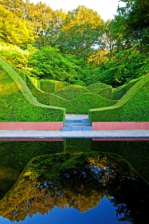 Veddw House Garden, Monmouthshire, Wales. Designed and created by Anne Wareham and Charles Hawes. July. The Reflecting Pool and Hedge Garden with view to the Coppice. Yew Hedges (Taxus baccata) for thinkingardens