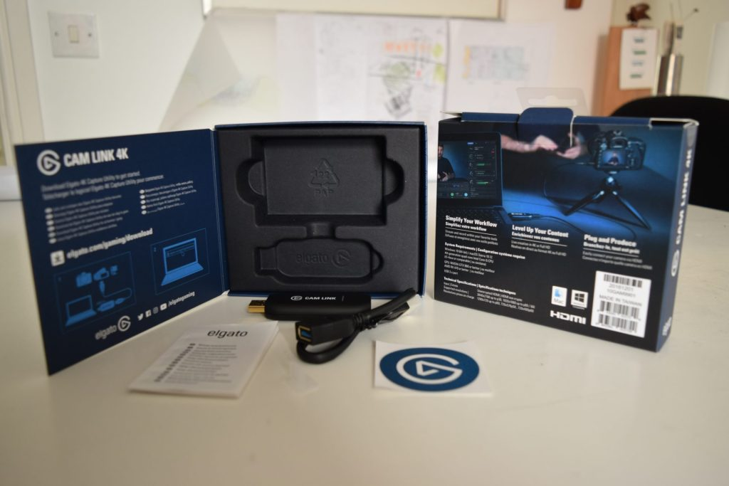Elgato Cam Link 4K , optional cable, little white guarantee card and a cool sticker. Plus with all shipping materials. The box is mainly blue and black with white writing. This contains the instructions for use. It is a device to convert camera to webcam