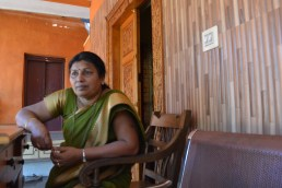 Mrs Nayana sitting at the porch of her house, talking.