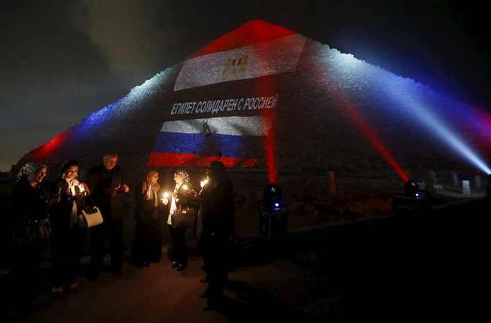 Egyptians light candles as the Russia and Egyptian flags and Russia's national colours of blue, white and red are projected onto one of the Giza pyramids