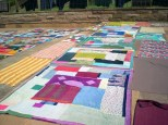 Colourful bedsheets spread to dry after being washed in the lake.