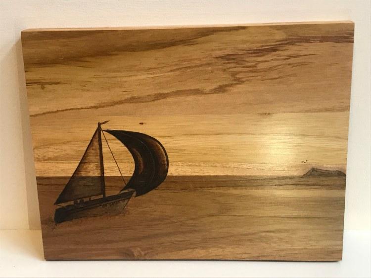 Zeilboot op zee bij ondergaande zon. De nerven van het hout geven de lucht en zee haar patroon.