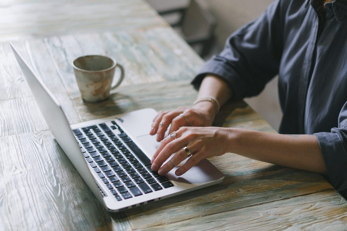 woman typing in her laptop and drinking coffee