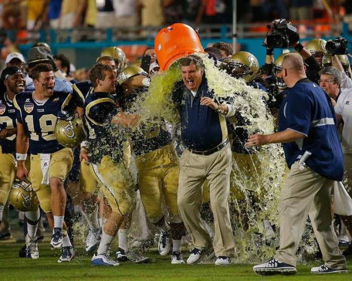 coach has water poured over him by happy players
