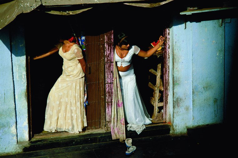"Prostitutes, who are known as cage girls and are often sex slaves, display themselves on a Mumbai street. Photo credit: Jodi Cobb/National Geographic ""Women of Vision"" exhibit"