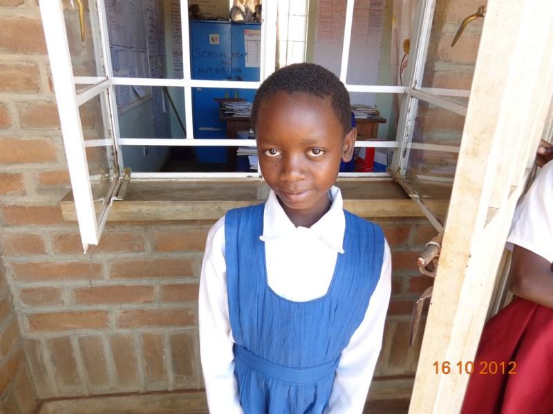 Malawi: Girl Smiles for the Camera A girl smiles for the camera outside the classroom in Malawi, Photo Credit: GPE/Deepa Srikantaiah