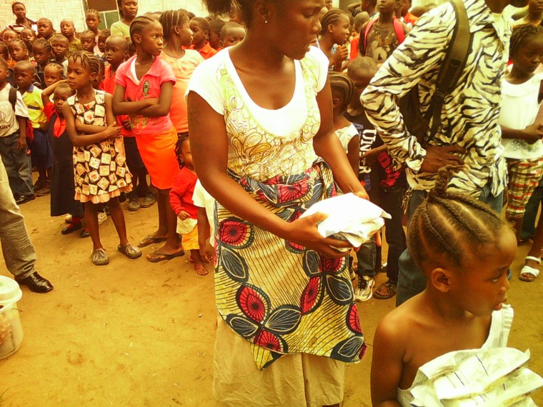 In July 2014 in Sierra Leone, a health worker, wearing head-to-toe protective gear, offers water to a woman with Ebola virus disease (EVD), at a treatment centre for infected persons in Kenema Government Hospital, in the city of Kenema, Eastern Province. A young boy stands nearby. Workers in the treatment centre are stretched to capacity. UNICEF is supporting the hospital by providing treatment supplies like intravenous fluids and equipment such as protective gear and body bags. Photo credit: New Vision