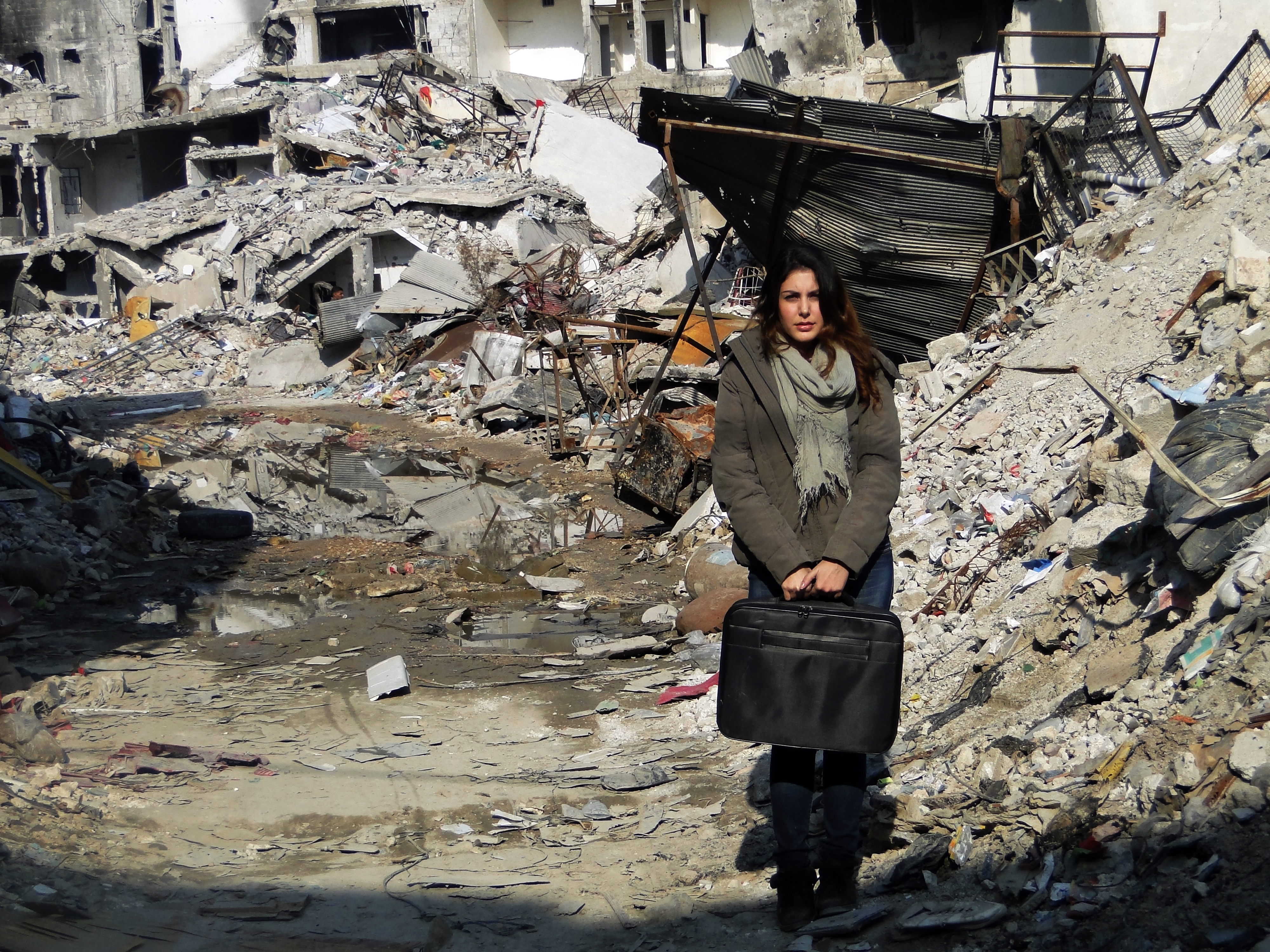 Abeer standing amidst the ruins. Photo credit: SOS Children's Villages
