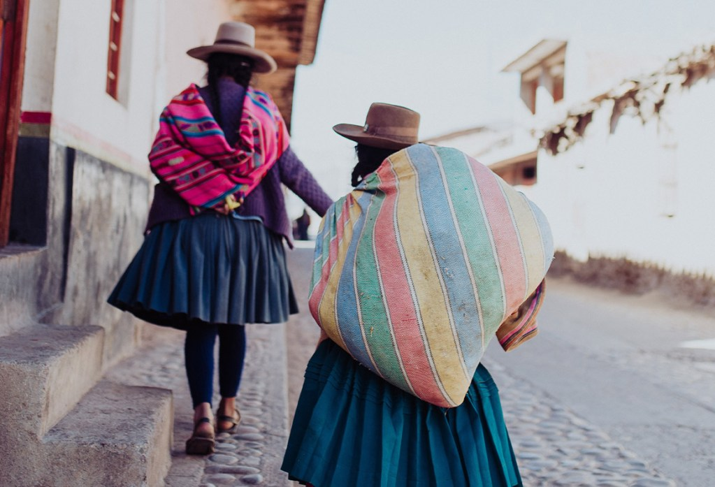 women in peru walking with our palo santo over shoulders