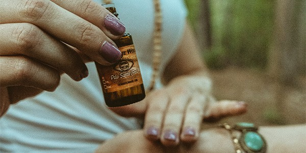 girl rubbing palo santo essential oil on her skin to repel insects
