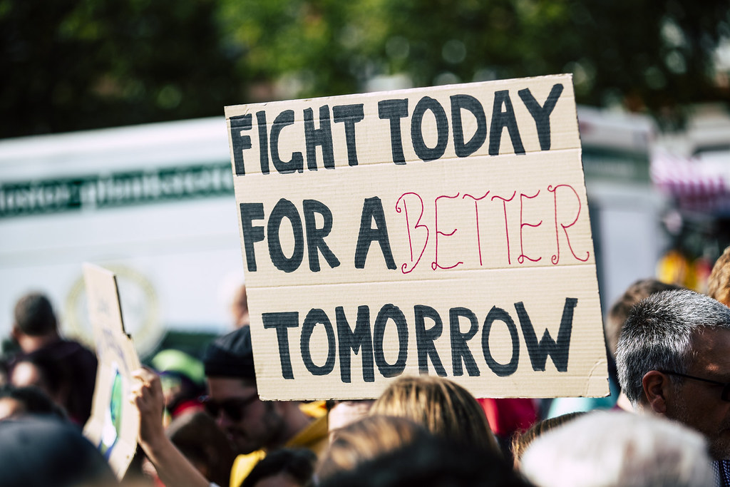 A Person Lobbying For Sustainability At A Climate Change Protest Holds A Sign That Reads Fight Today For A Better Tomorrow