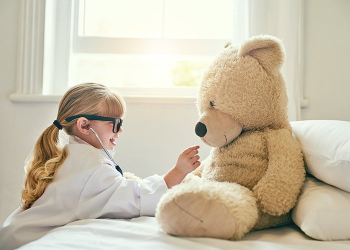 A little girl playing doctor with her teddy bear.