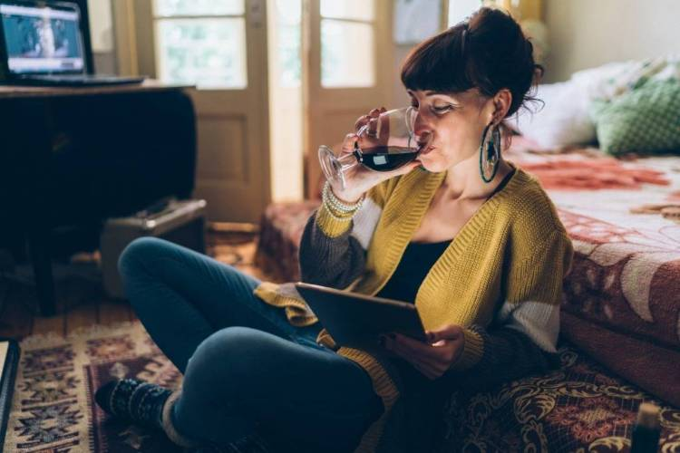 woman drinking wine and reading an e-book