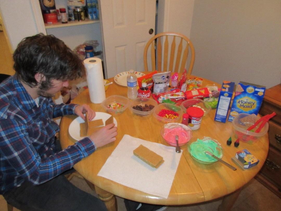 Taylor making graham cracker gingerbread houses