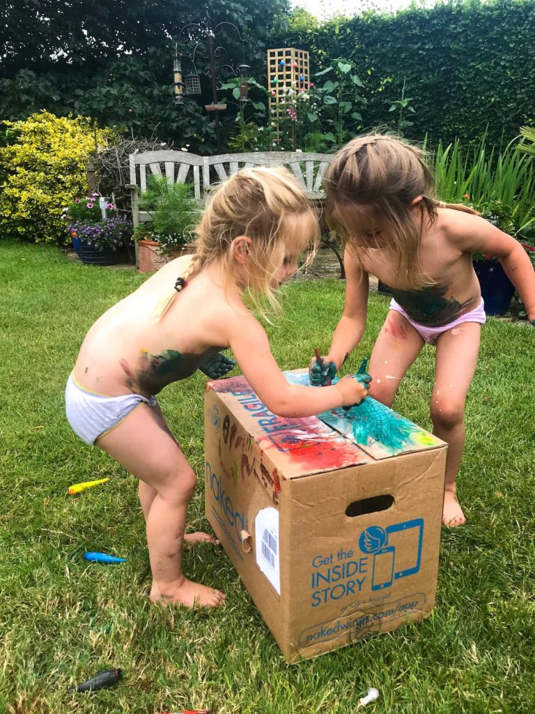Kids painting a cardboard box