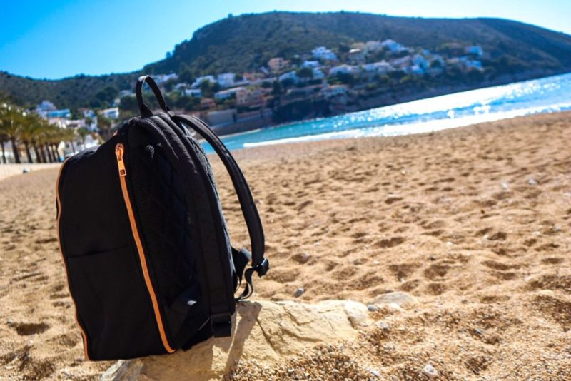 The Travel Hack carry-on backpack for women on El portet beach