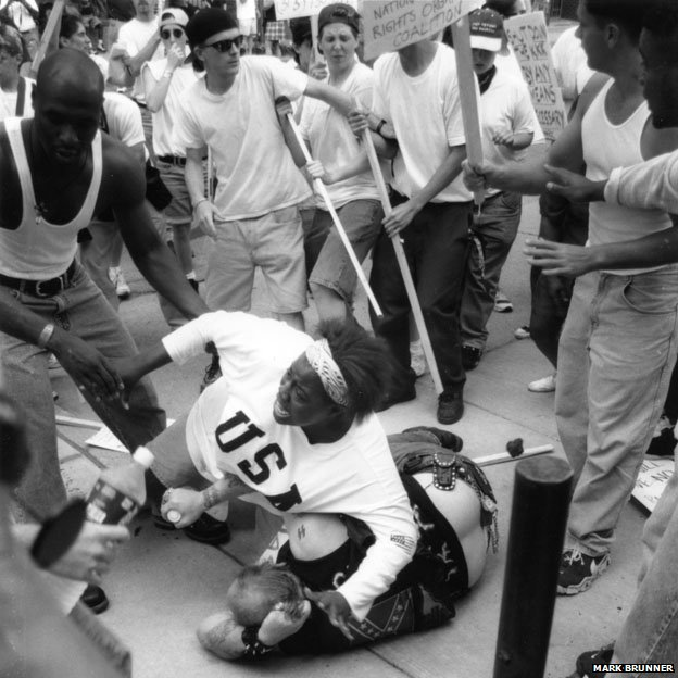 A black teenager protects a white man who was thought to be a Klu Klux Klan member from an angry mob in 1996.