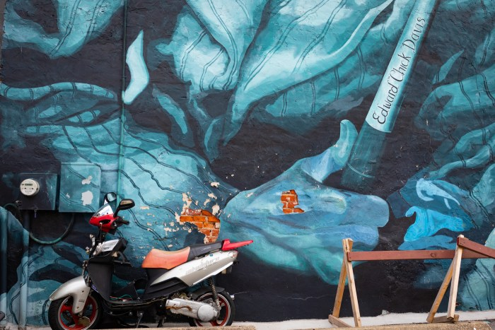Red Scooter and Bricks against Blue Mural