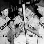 Teammates of Pat Seerey, with bat, gather around the Chicago White Sox leftfielder on July 18, 1948 in Philadelphia to extend their congratulations to him after he tied the major league batting record by hitting four homers in the first game of a doubleheader with the Philadelphia Athletics. Seerey bestows a kiss on the bat he used to pound out the record tying home run. Teammates not identified.