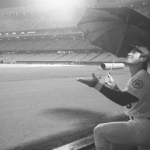 April 12, 1976: Los Angeles Dodgers first baseman Steve Garvey shields his head with an umbrella while watching rain fall at Dodger Stadium. After a 75-minute delay, the scheduled home opener was postponed. (Joe Kennedy / Los Angeles Times Archive/UCLA)