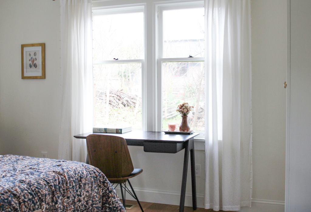 Dark wood midcentury style desk in front of windows.