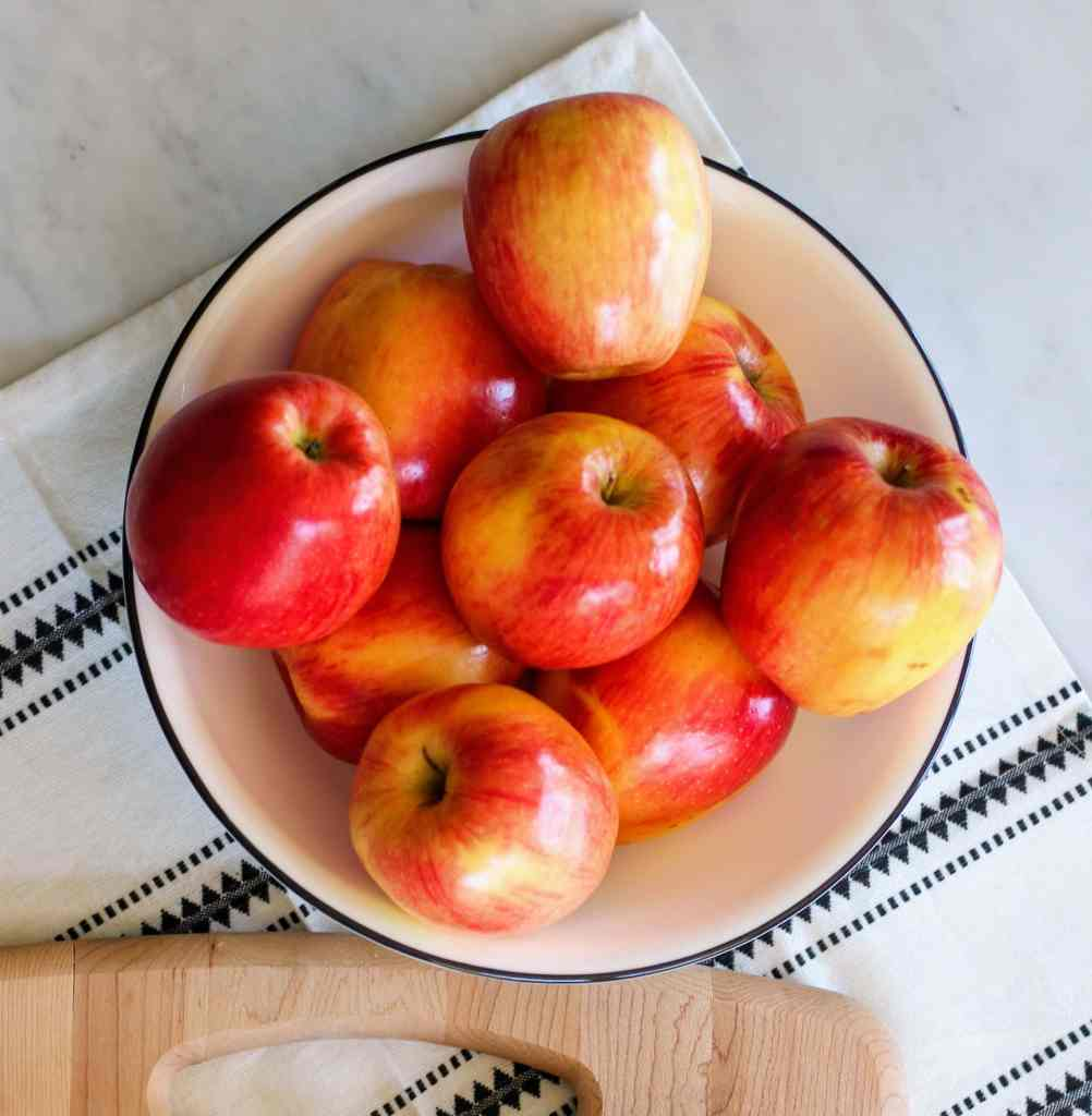 White bowl full of apples.