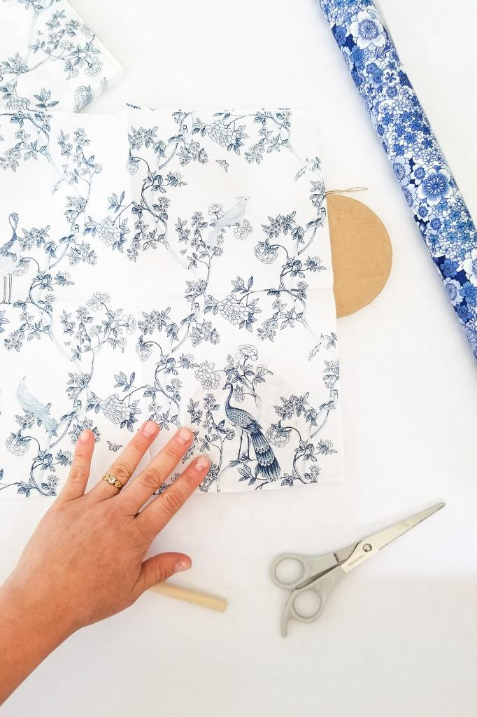hand pressing blue and white napkin on ornament